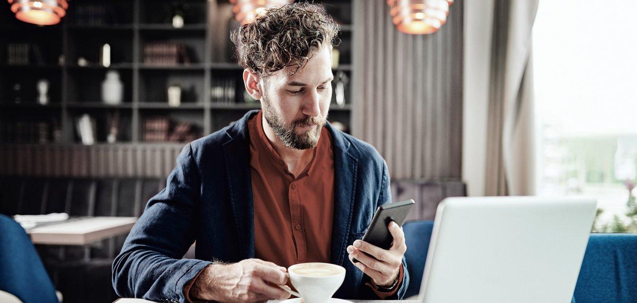 Mann in Cafe mit Smartphone