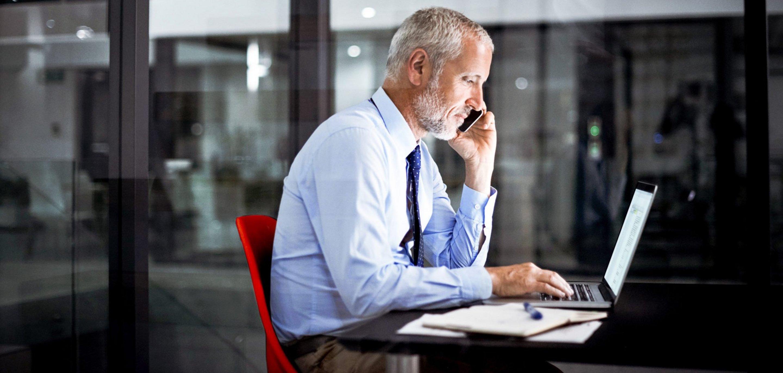Mann am Laptop mit Smartphone.