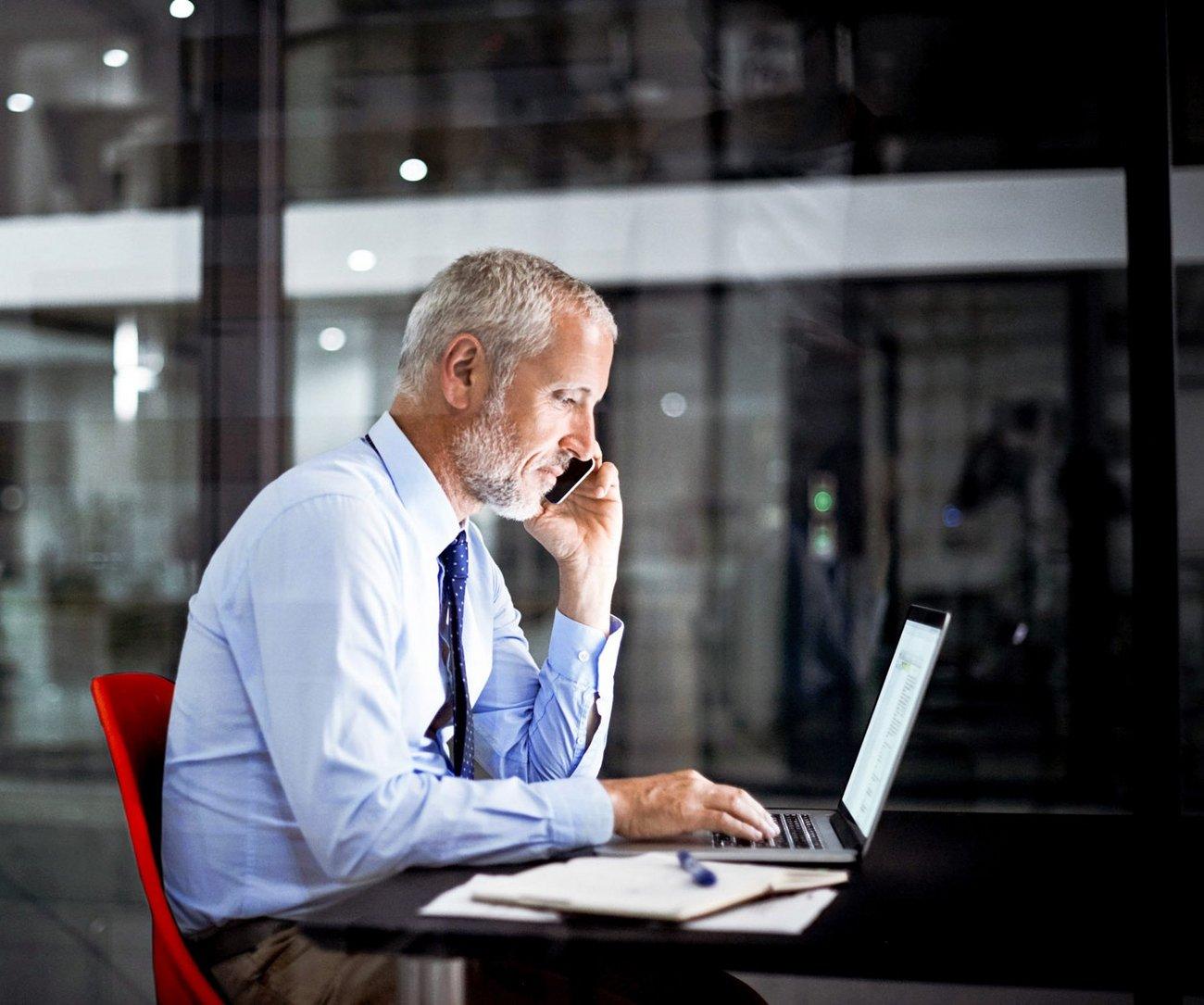 Mann am Laptop arbeitet und telefoniert.