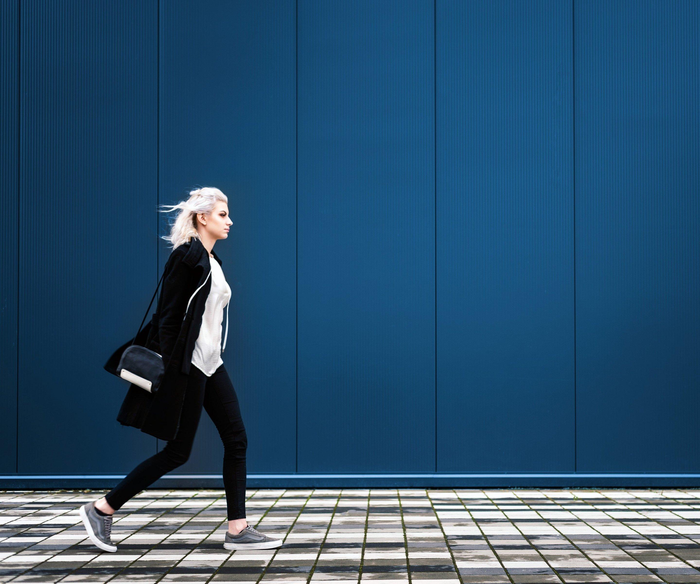 Frau läuft schnellen Schrittes auf Asphalt vor blauer Wand.